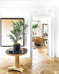 An Indoor Coffee Plant sits proudly on a circular hall table waiting to greet its owner.